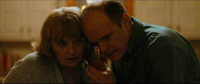 Jesse's parents huddle together to take a phone call from Jesse