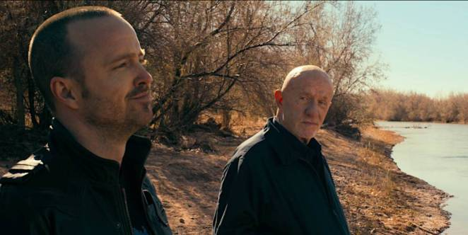 Mike Ehrmantraut looks at Jesse Pinkman as they stand on a riverbed