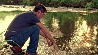 Jack looks at his hands as he kneels by the river