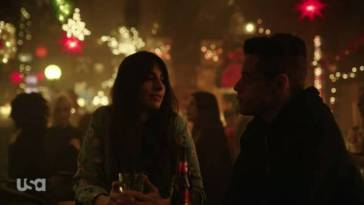 Olivia looks at Elliot with her hands on her drink as they sit together at a bar table