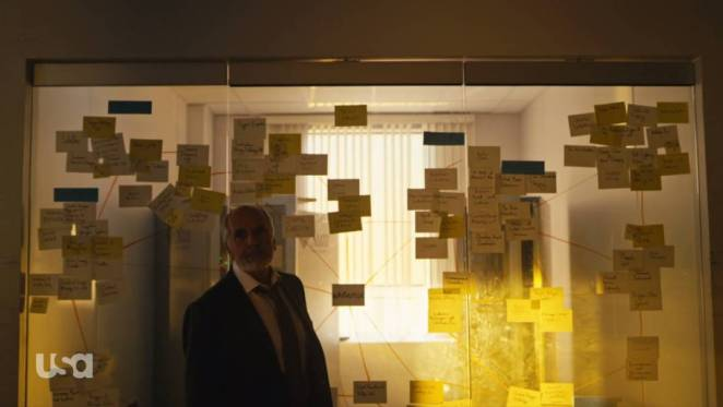 Price stands in front of Elliot's board of post-it notes
