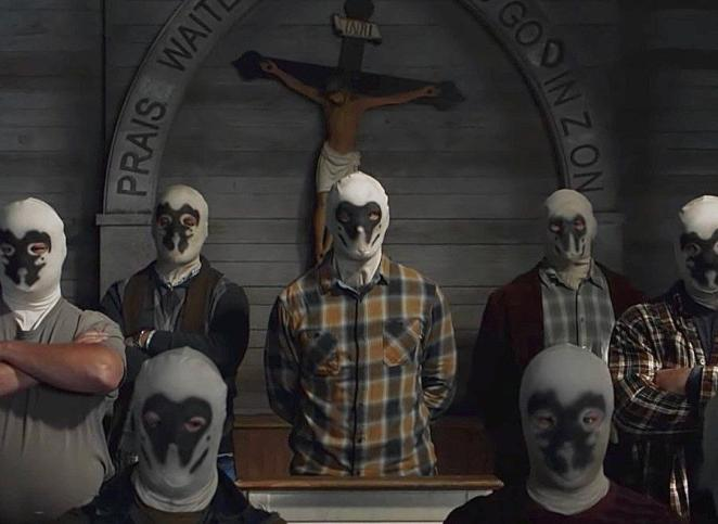 Men from the Seventh Kalvary wear Rorshach masks in a church