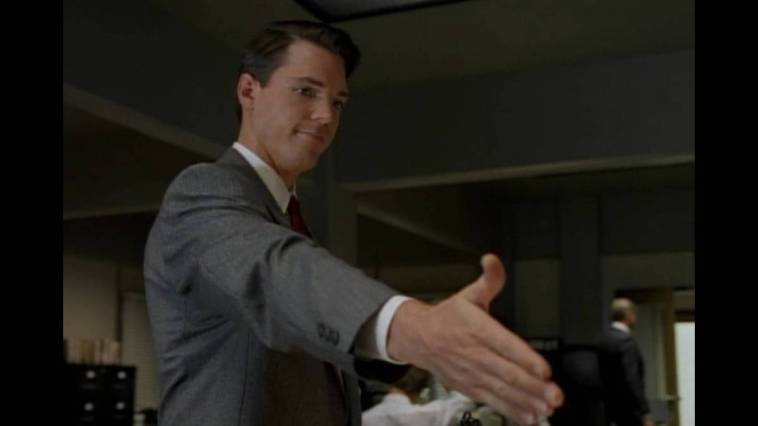 Alex Krycek, reaches out overdramatically to offer to shake Fox Mulder's hand in their tense first meeting.