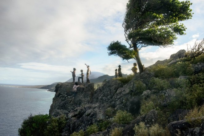A group of children hover over a cliff's edge looking at the ocean