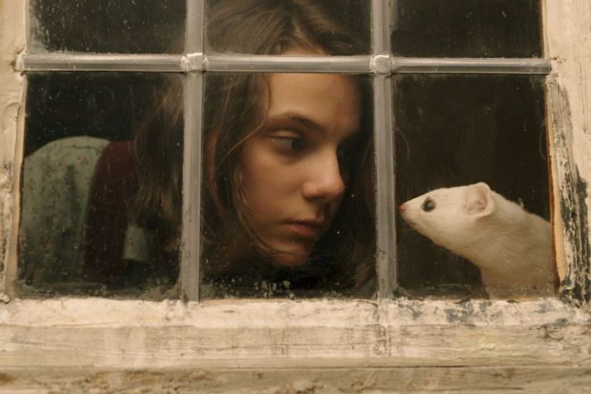 Lyra looking at Pan who is in the form of a small white ferret, through a closed window