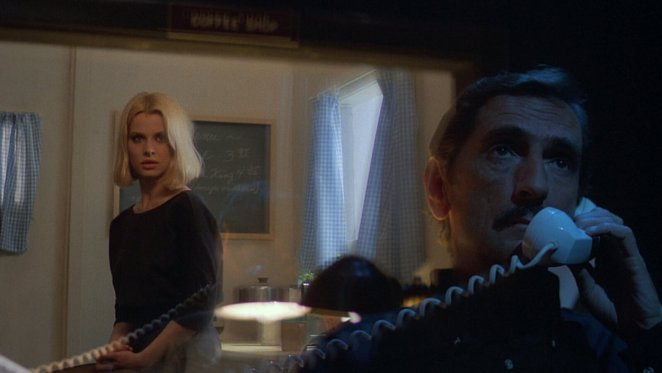 Travis confesses his sins to Jane in the peep room behind one-way glass, his back to her