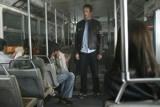 House stands in the middle of a bus, studying the other passengers.