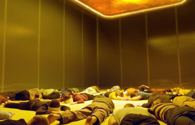 A room of people laying face down on the floor