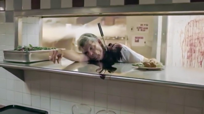 A diner cook lies dead over the counter, a large knife in his back