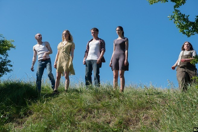 The five main characters, two women and three men, stand on a grassy hill.