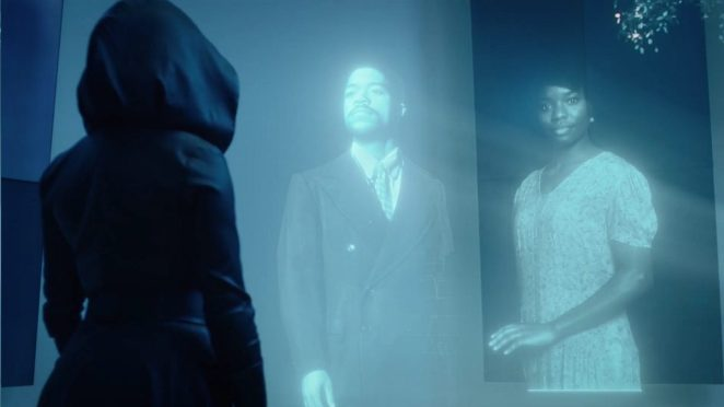 Sister Night looks on holograms of her great grandparents