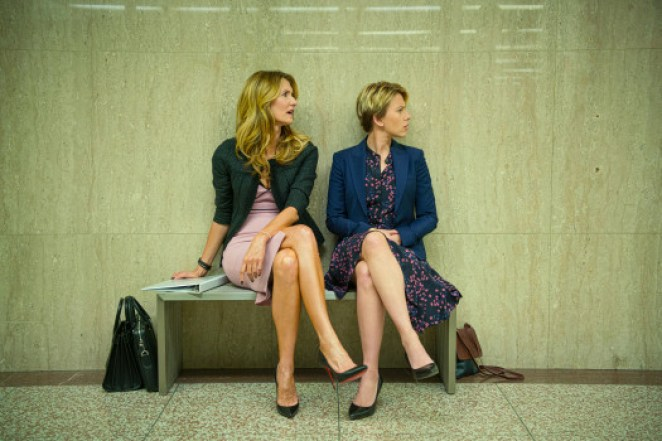 Nora and Nicole sit on a bench in the corridor looking to their left