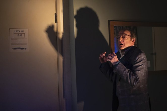 Robert looks on in fright, with his shadow on the wall behind him