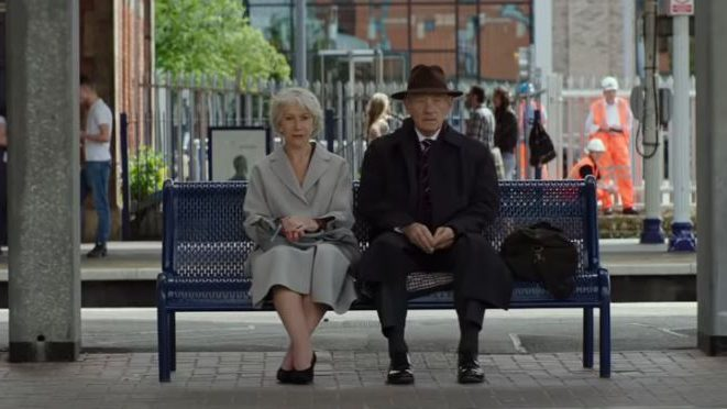 A man and a woman sit on a bench at a train station