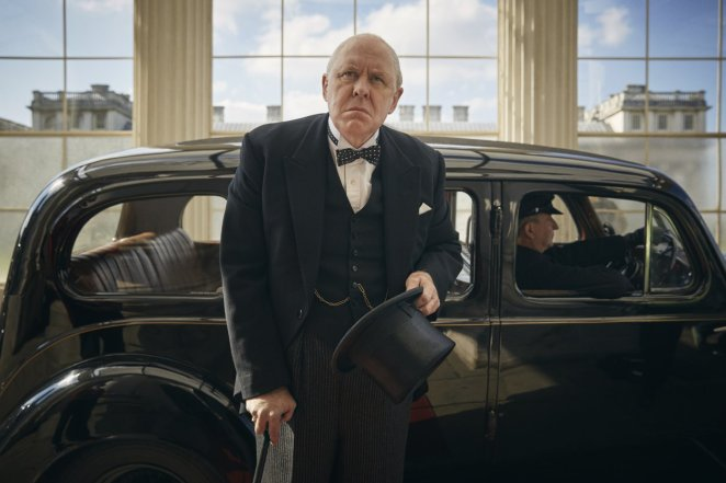 Winston Churchill steps out of a car at Buckingham Palace wearing a black suit and carrying a top hat