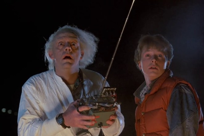 Marty McFly and Doc Brown staring at something in awe; Doc is holding a remote control.