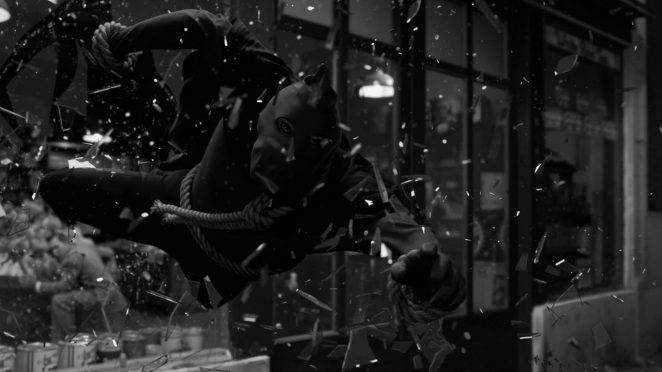 Hooded Justice dives through the front window of a grocery store in Watchmen