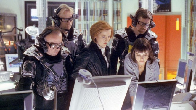 Scully, the Lone Gunmen wearing game gear, and a software programmer crowd around a computer monitor.