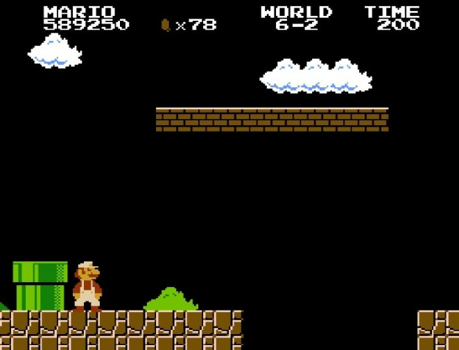 Super Mario stares down a very long jump in the darkness of World 6-2.