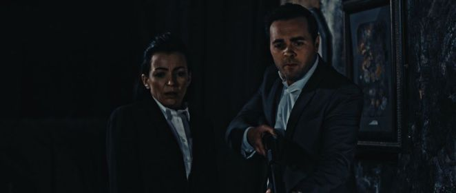 Jenna and Karl (holding a shotgun) in a still from Don't Let Them In