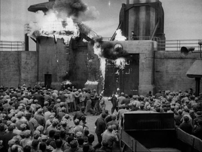 The prison tower is in flames in the background, with a crowd of inmates in foreground