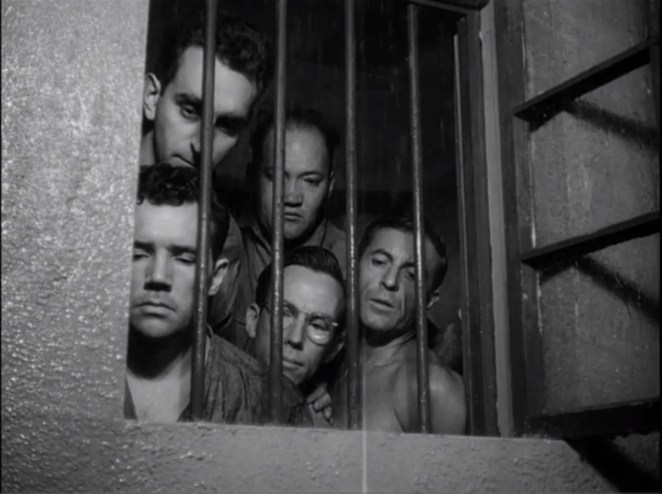 Five prisoners look out the window throw the bars of a cell