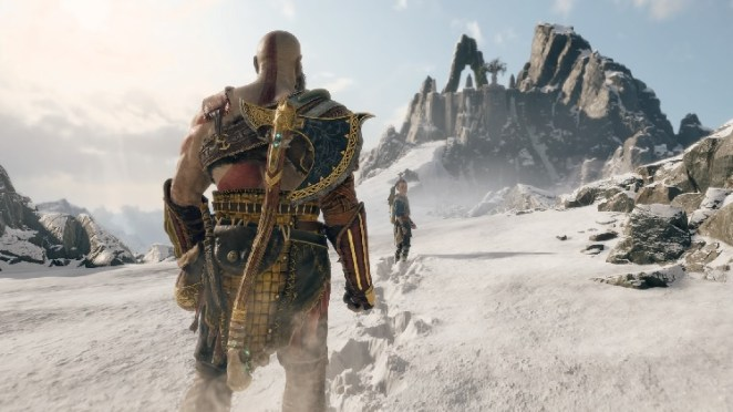 Kratos, a gigantic warrior with an ax strapped to his back, follows his young son through treacherous snow as they scale a tall mountain.