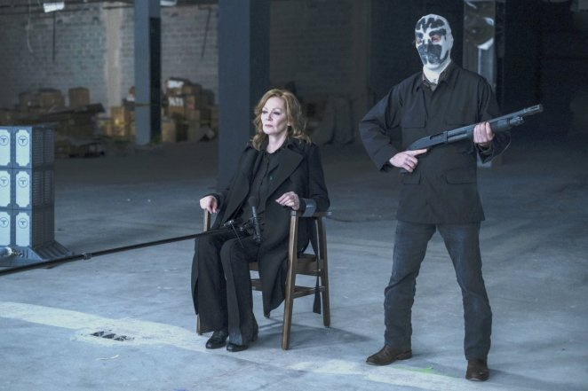 Laurie tied to a chair with Looking Glass disguised as a Seventh Kavalry member next to her with a shotgun