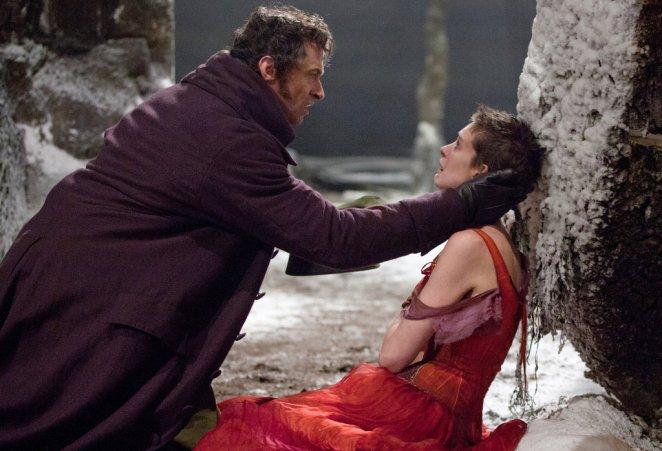 Fantine lies in the street, Valjean kneels down to help her