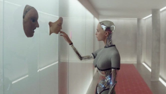 Ava touches a copy of her face on a shiny wall in a bright hallway