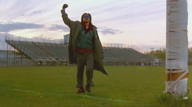 John Bender raises his fist triumphantly in the air as he walks across a school football field
