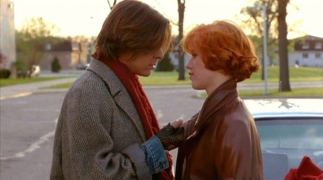 John Bender and Claire Standish face each other in a tender moment together in the school parking lot at the end of their detention day