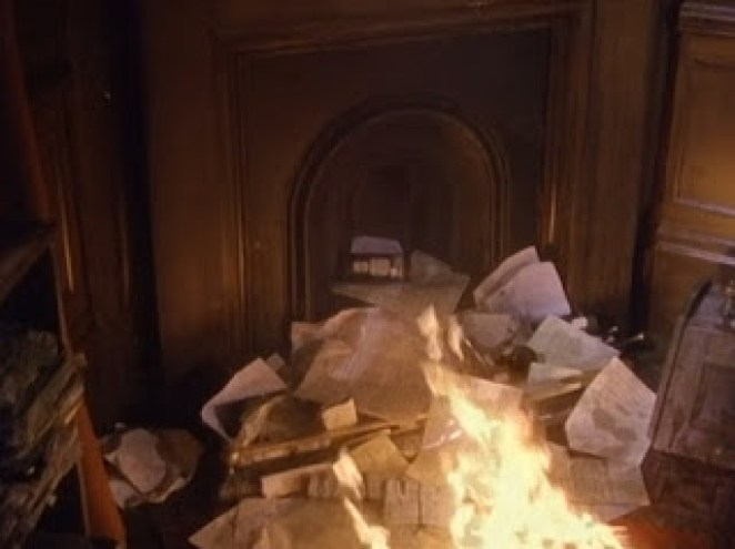 A fire place spilling out with papers on fire