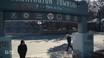 Elliot walks under a Washington Township sign that has been graffittied