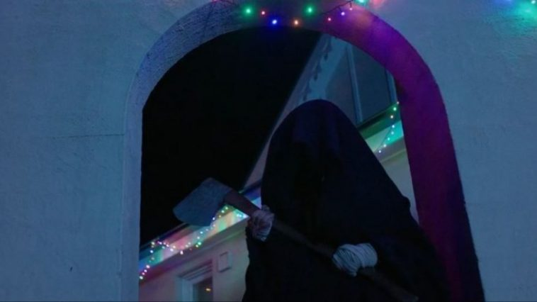 Cletus stands in a black cloak and holds an ax outside of the house in Red Christmas