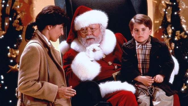 Santa talking to a mom while a boy sits on his knee