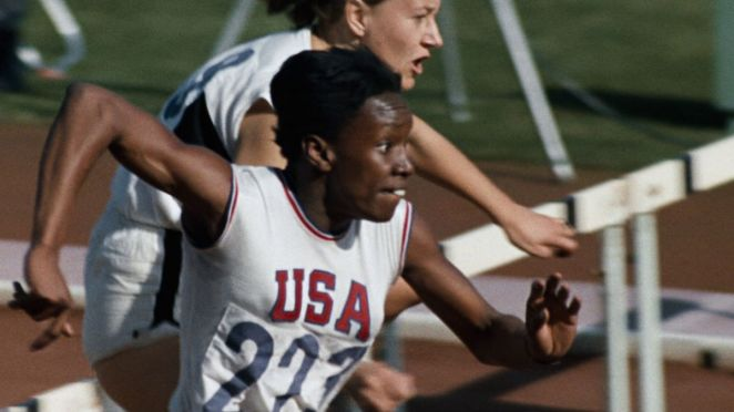 A track star jumps over a hurdle with another racer just behind her