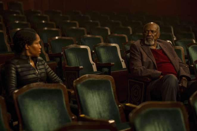 Angela and Will sit in the theater talking