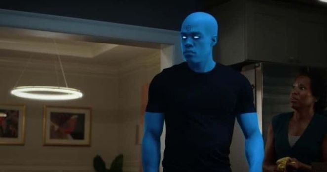 A reawakened Dr. Manhattan stands in his living room.