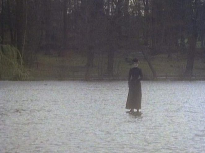 The Woman in Black stands on the lake staring at the Kidd family