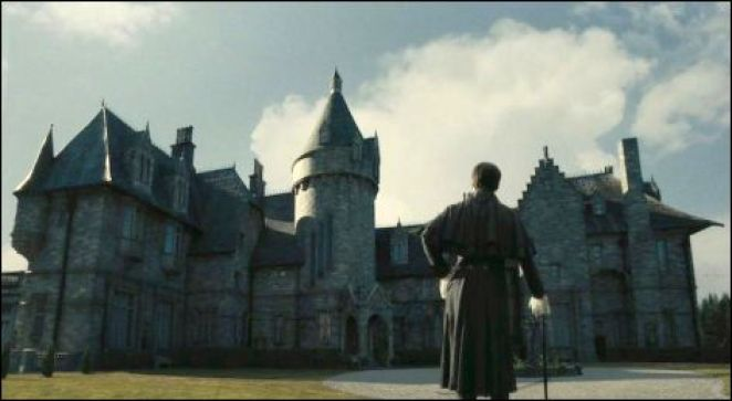 A man in the foreground looking up at a huge Gothic style estate known as Collinwood.