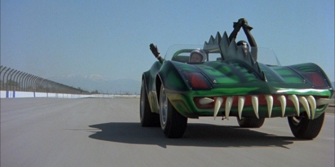 Frankenstein's green death mobile with sharp fins and gnarly teeth on the front bumper