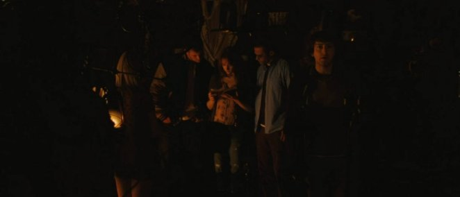 The youths stand in the cellar as Dana reads from a diary