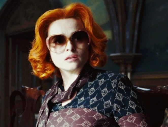 A woman with red hair, looking confused, in a 70's style shirt and large glasses