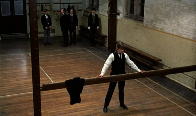 Mick assumes the position on the school gym apparatus, as The Whips prepare to cane him