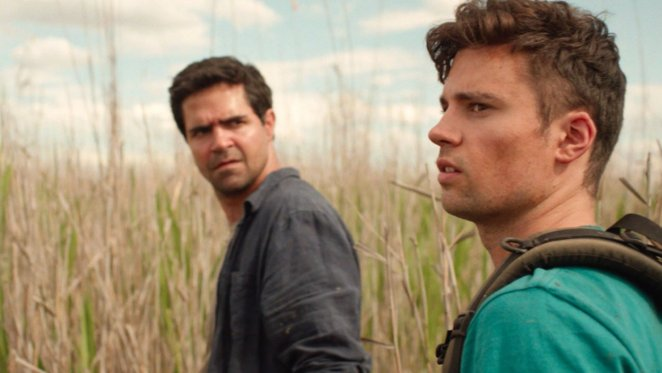 Ben stares angrily at Will who looks at something off screen while lost in a marsh