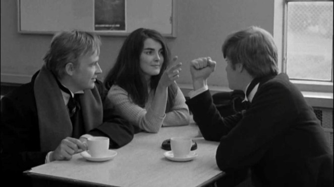 Mick, Johnny and The Girl play Rock, Paper, Scissors at a cafe table