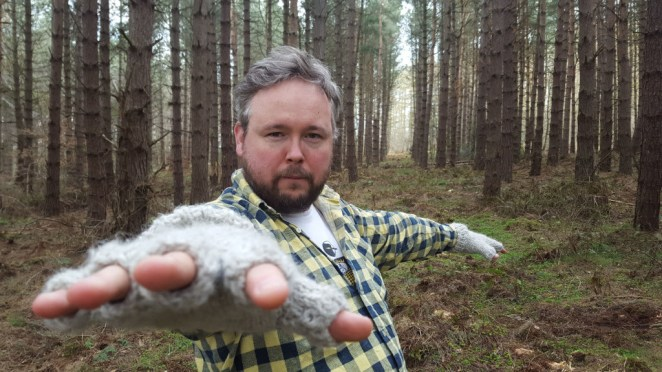 Richard Dawson stretches a hand forward as he stands in front of trees