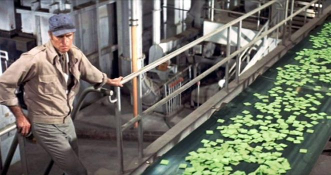 Thorn walks on the assembly line carrying Soylent Green