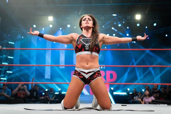 Tessa Blanchard with arms stretched out on her knees in the ring